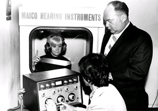 Co-op student John Schwab, seated, conducting hearing test while Larry Carter, owner and president of Malco Boston Company, oversees testing, 1974.